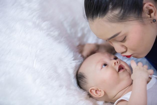 Las familias, los padres y los bebés yacen en la cama en la sala de estar.