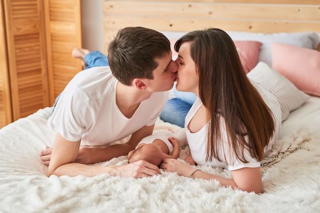Famiy padres jóvenes con un bebé recién nacido en casa en la cama