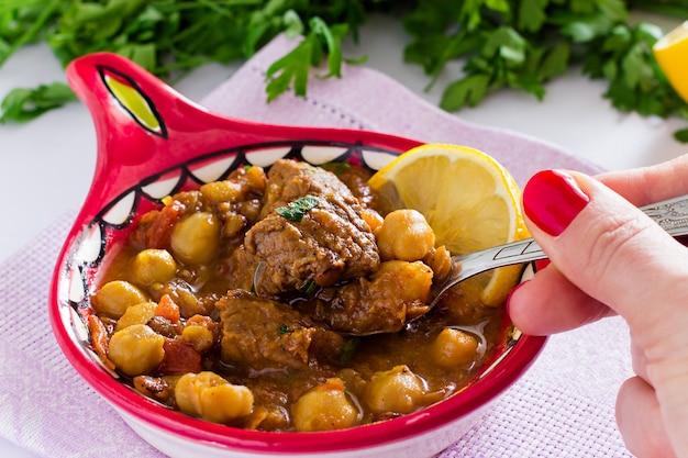Famosa sopa de harira marroquí con carne, garbanzos, lentejas, tomates y especias. caluroso, fragante. preparándose para iftar en el mes sagrado de ramadán