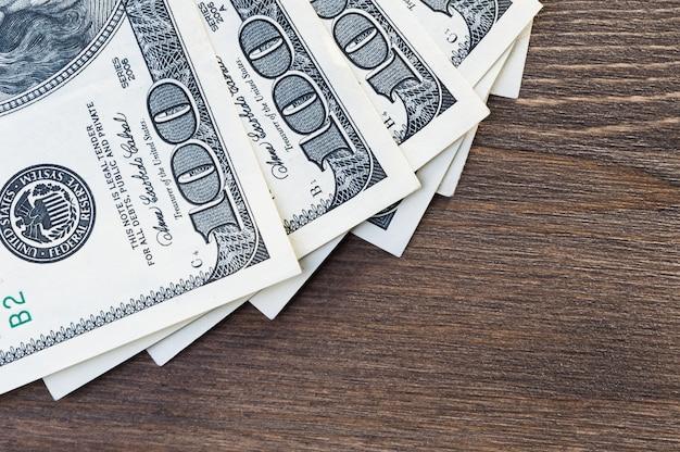 Un fan de billetes de cien dólares sobre un fondo de madera oscura. vista desde arriba.