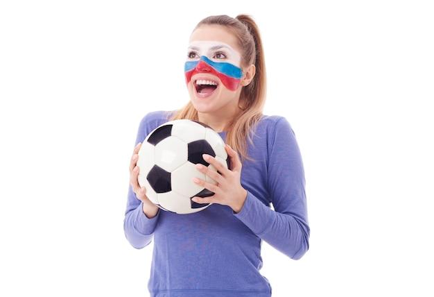 Fan femenino extático con vítores de balón de fútbol