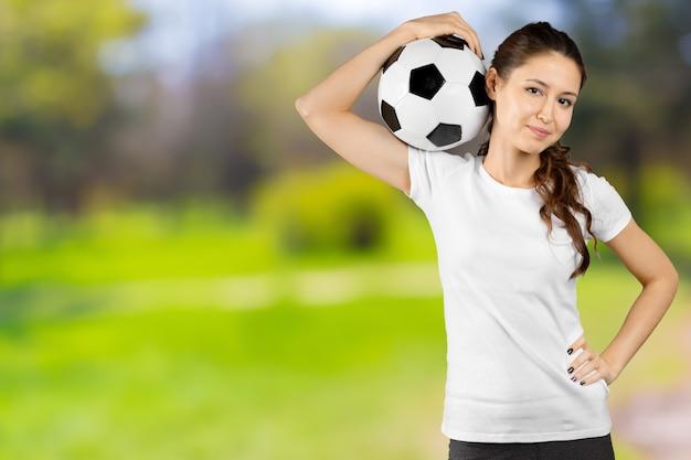 Fan del fubol. mujer hermosa joven que sostiene el balón de fútbol sobre aislado