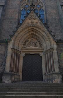 Faña de la iglesia gótica con hermosas puertas y ventanas en praga