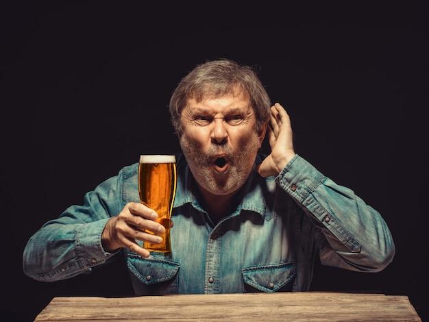 El fanático encantado y emocional con un vaso de cerveza.