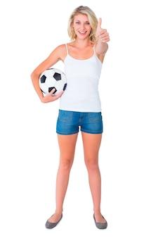 Fanático del fútbol bastante rubio sosteniendo la bola que muestra los pulgares para arriba