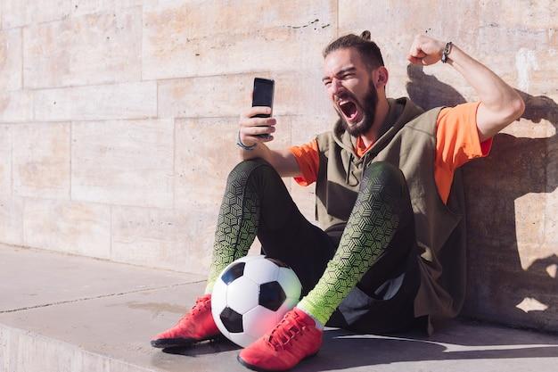 Fanático del fútbol celebrando la victoria teléfono de consultoría