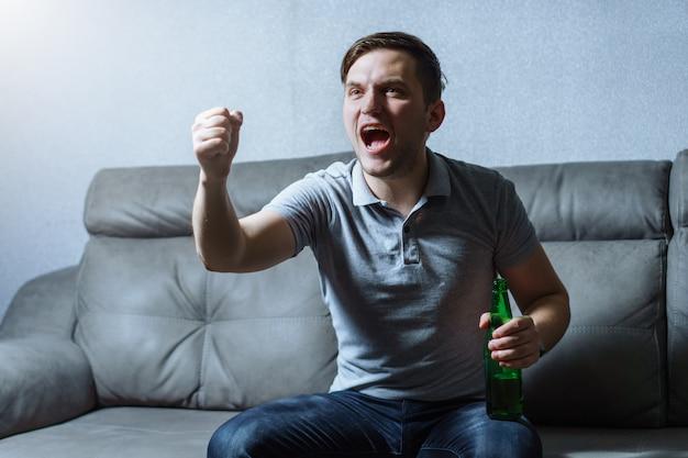 Fanático del fútbol viendo televisión en un autocar con cerveza y gritando