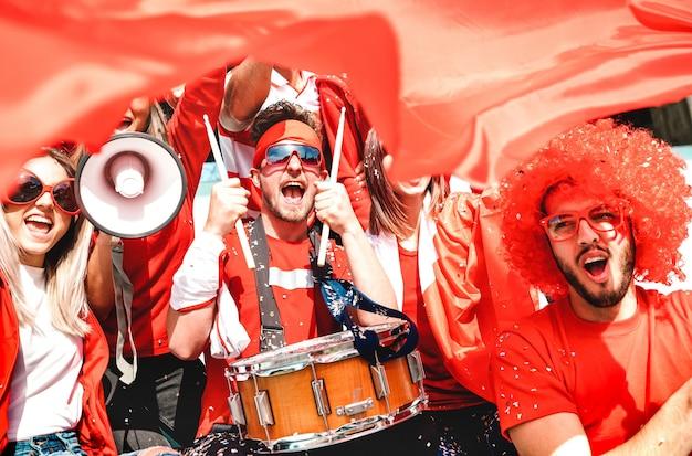 Los fanáticos de los aficionados al fútbol animando con la bandera viendo el partido de la copa de fútbol en la tribuna del estadio