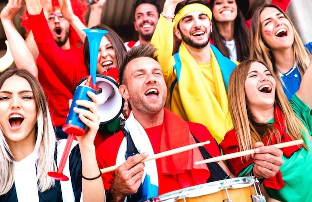 Los fanáticos de los aficionados al fútbol animando con tambores viendo el partido de la copa de fútbol en las gradas del estadio