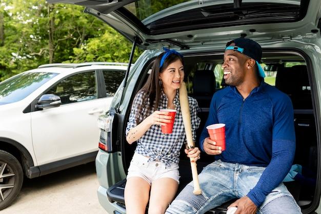 Los fanáticos del béisbol sentado en el maletero del coche en una fiesta en el portón trasero