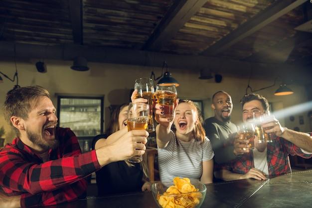 Fanáticos del deporte que animan en el bar, pub y beben cerveza mientras el campeonato, la competencia continúa