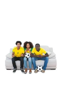 Fanáticos del fútbol brasileños nerviosos en amarillo en el sofá