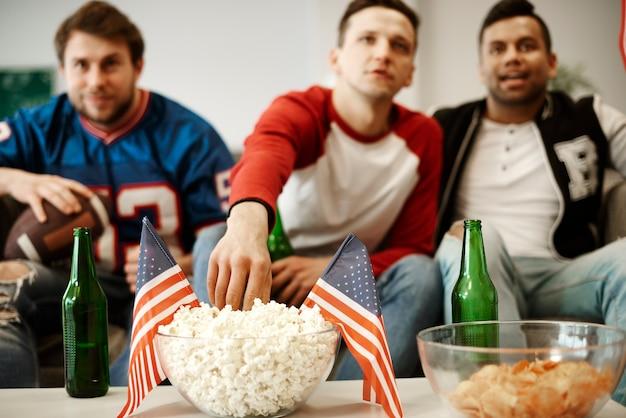 Fanáticos del fútbol comiendo bocadillos en casa