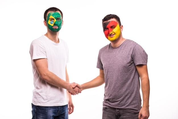 Los fanáticos del fútbol de los equipos nacionales de alemania y brasil con la cara pintada se dan la mano sobre fondo blanco.