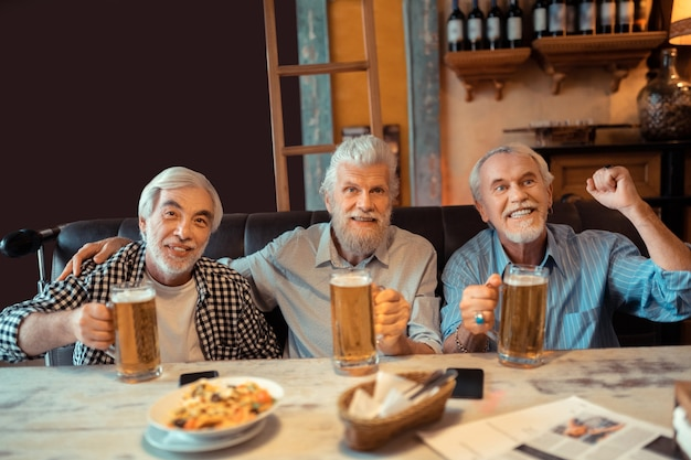 Los fans se emocionan. tres fanáticos del fútbol retirados que se sienten emocionados mientras ven fútbol