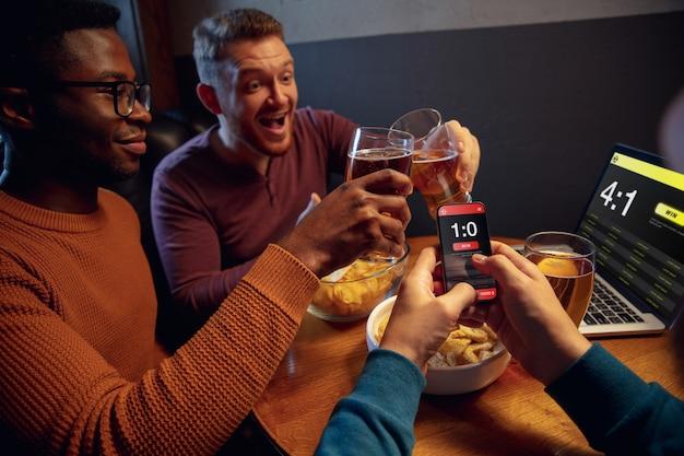 Fans entusiasmados en el bar con cerveza y aplicación móvil para apostar puntaje en sus dispositivos.