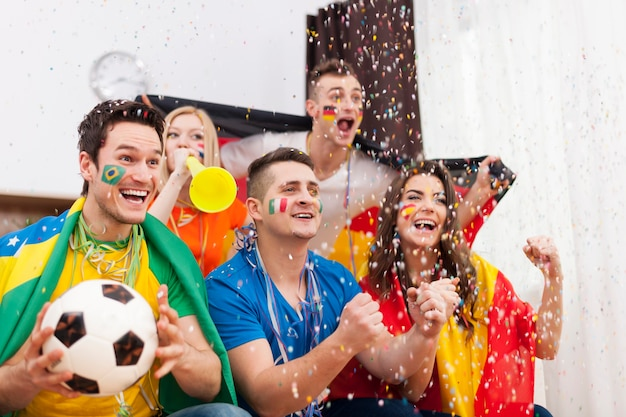Fans entusiasmados del fútbol celebrando el partido ganador