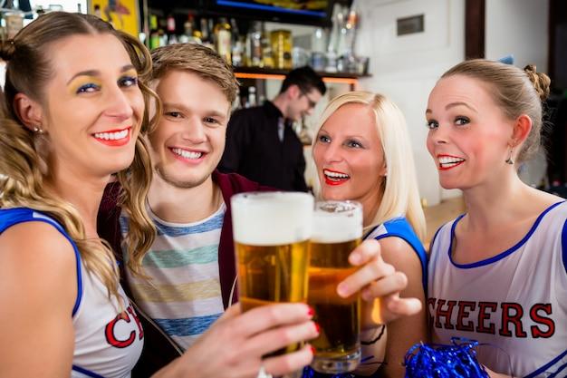 Fans de un equipo deportivo viendo un juego en un bar.