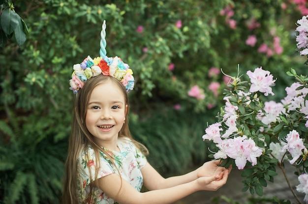 Fantasía niña con cuerno de unicornio arcoiris con flores en el parque azalea