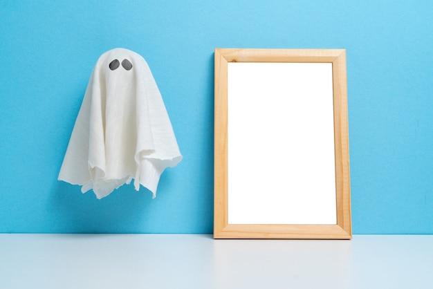 Un fantasma abstracto junto a un marco de madera con espacio de copia vacaciones de halloween