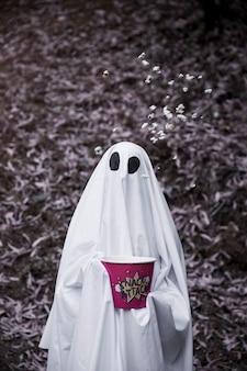 Fantasma con caja de palomitas de maíz y palomitas de maíz cayendo en el aire