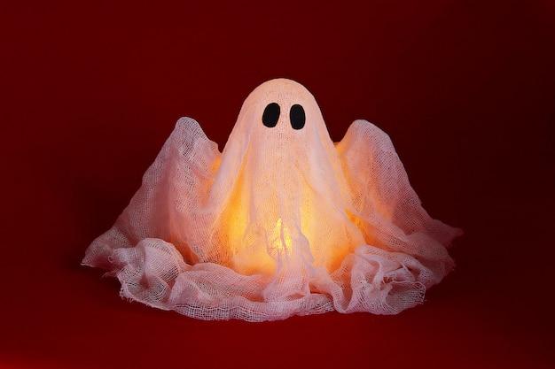 Fantasma de halloween de almidón y gasa sobre fondo naranja. idea de regalo, decoración de halloween.