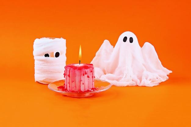 Fantasma de halloween de almidón y gasa sobre naranja.