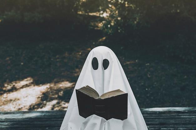 Fantasma leyendo libro abierto en el parque