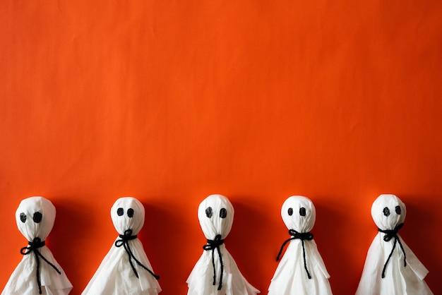 Fantasma de papel sobre fondo de papel naranja