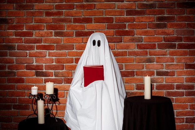 Fantasma que sostiene el libro sobre la pared de ladrillo. fiesta de halloween.