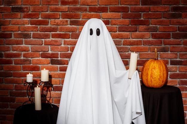 Fantasma que sostiene la vela sobre la pared de ladrillo. fiesta de halloween.