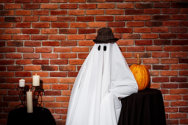 Fantasma con sombrero posando sobre pared de ladrillo fiesta de halloween.