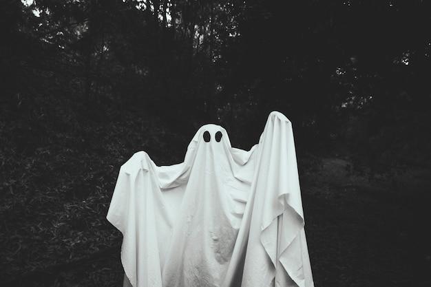 Fantasma sombrío con las manos en alza de pie en el bosque