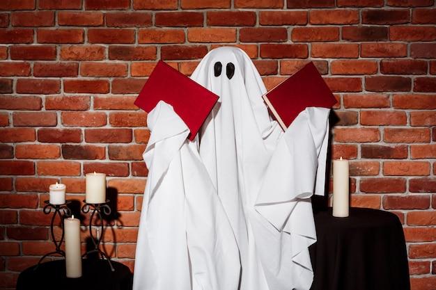 Fantasma sosteniendo libros sobre pared de ladrillo. fiesta de halloween.