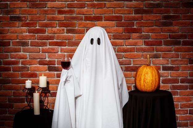 Fantasma sosteniendo vino sobre pared de ladrillo