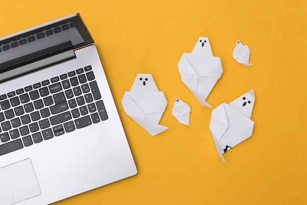 Fantasmas de ordenador portátil y origami sobre fondo amarillo. tema de halloween. vista superior