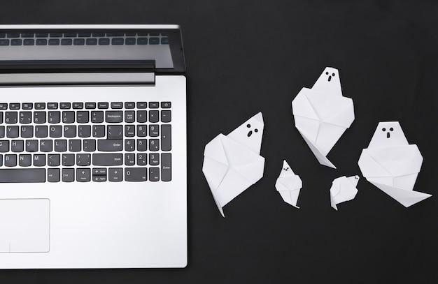 Fantasmas de ordenador portátil y origami sobre fondo negro. tema de halloween. vista superior