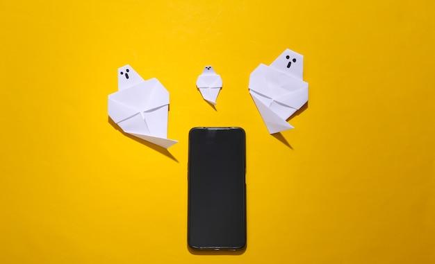 Fantasmas de origami y smartphone sobre fondo amarillo brillante. vista superior