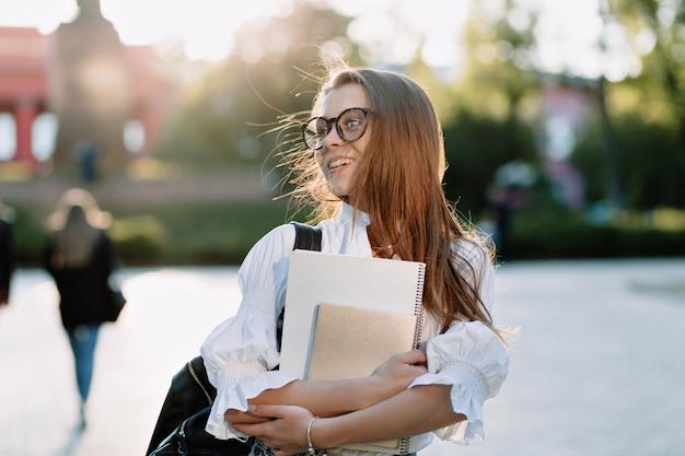 Fantástica feliz joven estudiante de regreso a la universidad con cuadernos y computadora portátil, yendo a la universidad con una sonrisa feliz en la calle soleada