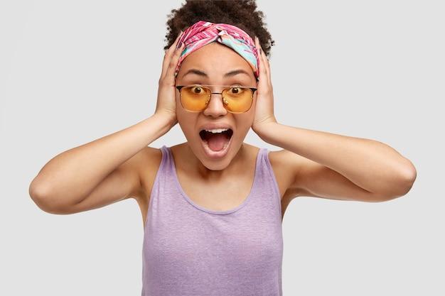 Fantástica joven linda mujer afroamericana con mirada inesperada de sorpresa, abre la boca ampliamente, vestida con una camiseta morada y una diadema, posa sobre una pared blanca, expresa una gran incredulidad