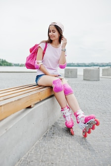Fantástica mujer joven en ropa casual y gorra sentado en el banco en el skatepark con patines en línea.
