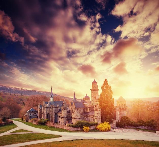 Fantástica puesta de sol con cúmulos sobre el antiguo castillo