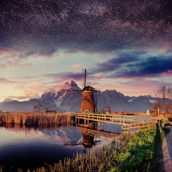 Fantástico shtrbske pleso high tatras. molino holandés en la noche.