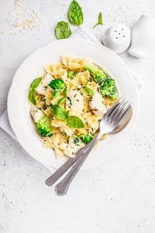 Farfalle de pasta italiana con brócoli, pollo y queso en un plato blanco.