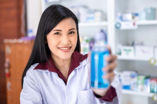 Farmacéutica asiática mostrar botella de gel para manos en farmacia