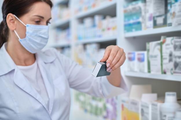 Farmacéutica seria centrada en elegir un medicamento para su cliente.