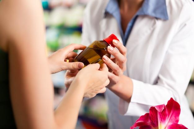 Farmacéutica en su farmacia con un cliente