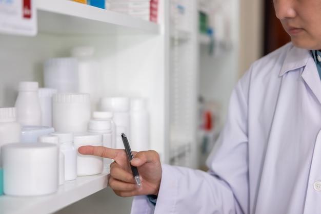Farmacéutico apuntando al frasco de medicina en la estantería de la farmacia