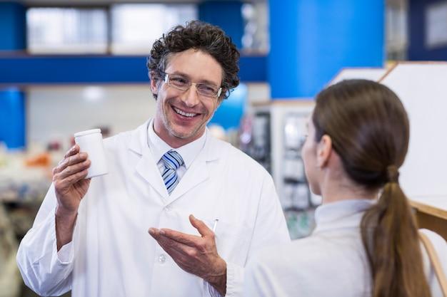 Farmacéutico asistiendo la botella de droga al cliente