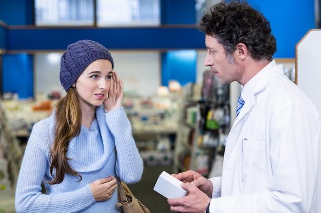 Farmacéutico asistiendo la caja de medicina al cliente
